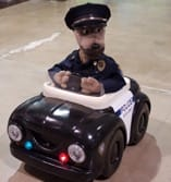 A stuffed animal dog driving a cop car