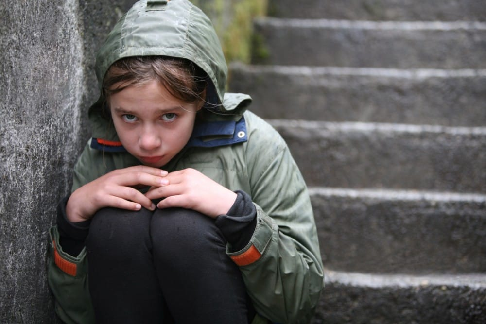 A girl sitting on steps who looks sad