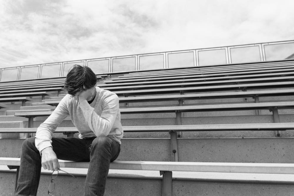 A boy sitting on bleachers with his hand on his head