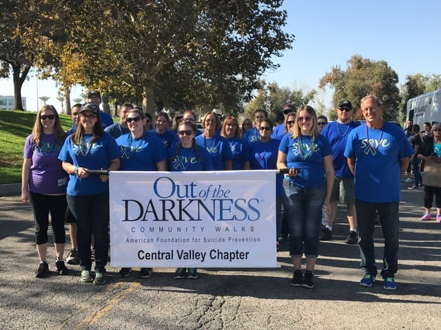 Group walking with an out of darkness banner